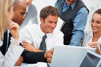Buy stock photo Closeup of executive in front of laptop with colleagues surrounding him