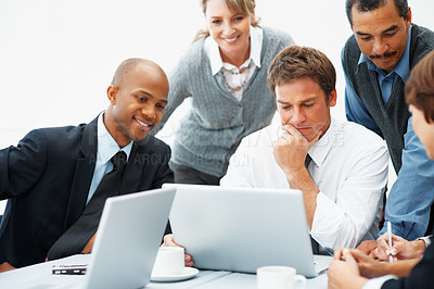 Buy stock photo Colleagues surrounding executive as he works on laptop