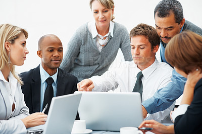 Buy stock photo Colleagues pointing to proposal on laptop while executives look on