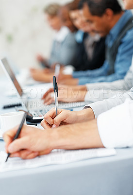 Buy stock photo Closeup of hands taking notes during business meeting with colleagues in background