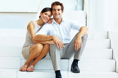 Buy stock photo Portrait of an attractive young couple sitting on steps of building