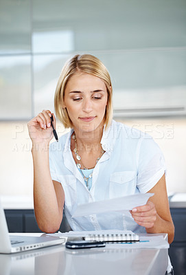 Buy stock photo Portrait of a charming young businesswoman holding pen and looking at contract paper at office