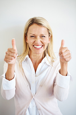 Buy stock photo Portrait of a happy young female showing goodluck sign against grey background
