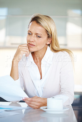 Buy stock photo Portrait of a thoughtful young woman reading a paper with cup of in office