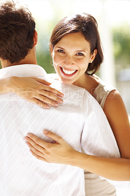 Buy stock photo Portrait of beautiful young woman hugging a man and smiling outdoors