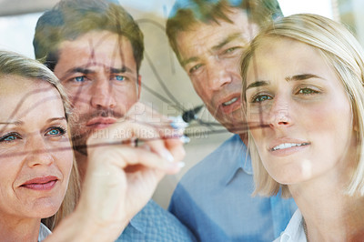 Buy stock photo Smart young businesswoman drawing a diagram on glass as her colleagues watch