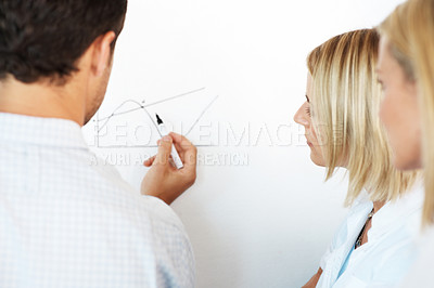 Buy stock photo Rear-view of a business team going over a graph together