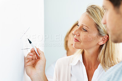 Buy stock photo Smart young businesswoman looking carefully at a diagram in her office