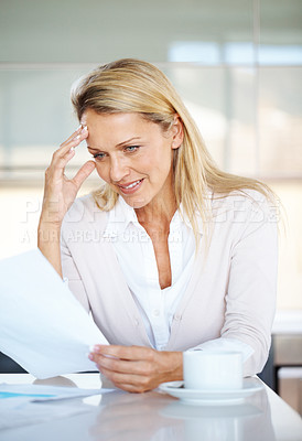 Buy stock photo Portrait of a beautiful young businesswoman reading a document at her desk in office