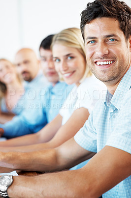 Buy stock photo Happy young businessman sitting in a seminar with his colleagues in background