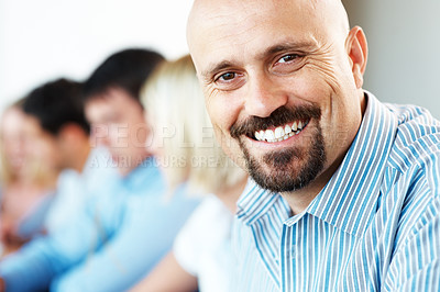Buy stock photo Closeup of a handsome mature businessman smiling in a conference with his associates in background at office