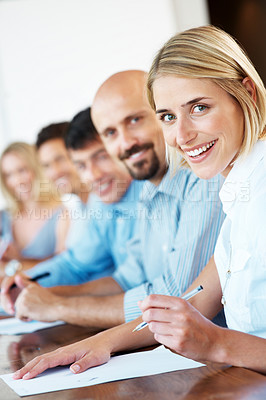 Buy stock photo Portrait of a happy young business woman taking notes during a seminar with her colleagues in background