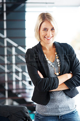Buy stock photo Portrait of a casual young businesswoman standing with her hands folded