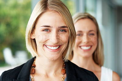 Buy stock photo Portrait of a cute young businesswoman smiling with her colleague in the background