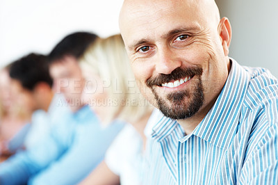 Buy stock photo Portrait of a happy young businessman attending meeting in office with his colleagues