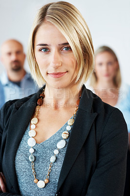 Buy stock photo Portrait of a confident young female with her business colleagues at office