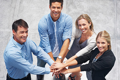 Buy stock photo Top view of happy business colleagues with their hands together gesturing unity