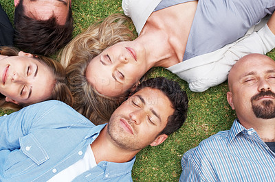 Buy stock photo Portrait of group of people lying together on grass taking a nap