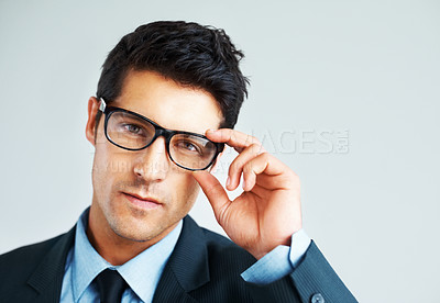 Buy stock photo Confident executive holding glasses while giving serious look