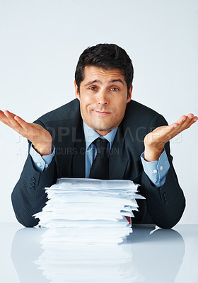 Buy stock photo Young man in suit sitting with paperwork looking overwhelmed