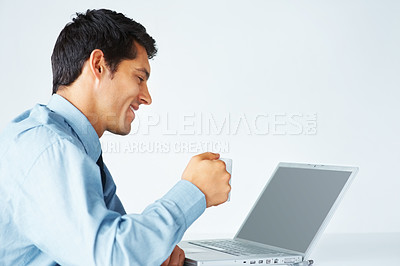 Buy stock photo Young businessman holding coffee cup and looking at laptop