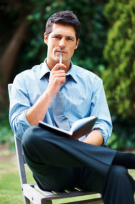 Buy stock photo Businessman sitting outdoors with book, looking thoughtful