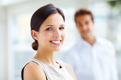Buy stock photo Portrait of happy young woman smiling with a man in background