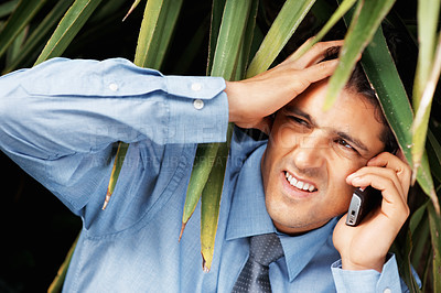 Buy stock photo Tensed businessman hiding under foliage while on cell phone
