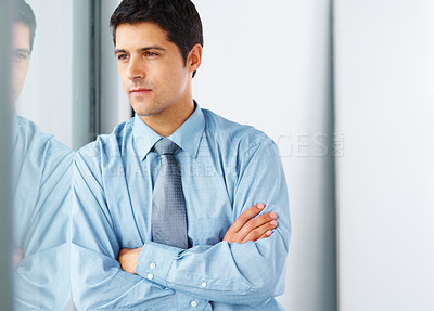 Buy stock photo Thoughtful business man looking out window with arms crossed