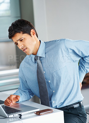 Buy stock photo Young business man sitting in front of laptop with severe back pain