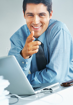 Buy stock photo Smart businessman smiling and pointing while sitting in front of laptop