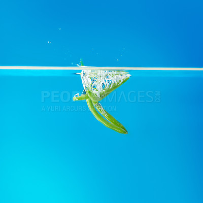 Buy stock photo View of green beans falling into water against blue background