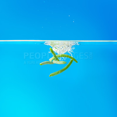 Buy stock photo Green beans falling into water against blue background