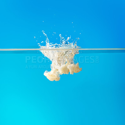 Buy stock photo View of cauliflower dropped into water, creating splash against blue background