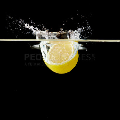 Buy stock photo Half lemon dropped into water against black background