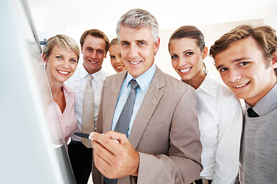 Buy stock photo Male leader with his team pointing at blank drawing board