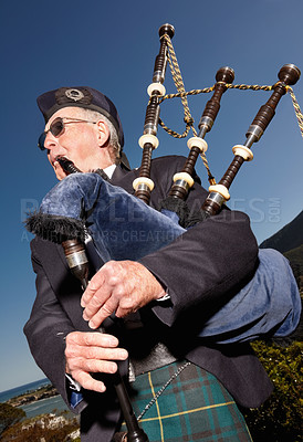 Buy stock photo Portrait of a mature highlander wearing kilt and playing bagpipes
