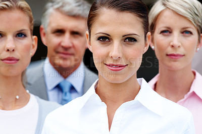 Buy stock photo Beautiful young business woman looking confidently with her staff in background