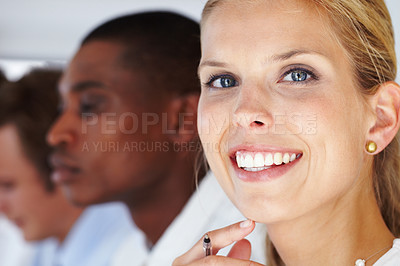 Buy stock photo Closeup of a beautiful young female business executive smiling with her colleagues in background