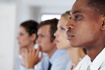 Buy stock photo Attentive young african businessman at a meeting with his colleagues in background