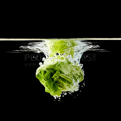 Buy stock photo View of head of lettuce falling into water against black background