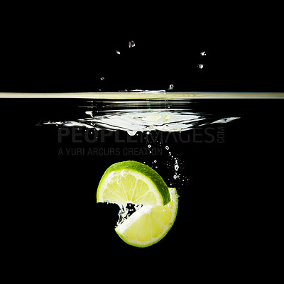 Buy stock photo Lime falling into water against black background