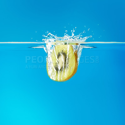 Buy stock photo Kiwi slice falling into water