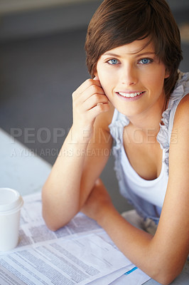 Buy stock photo Smiling young woman sitting at her desk with paper work
