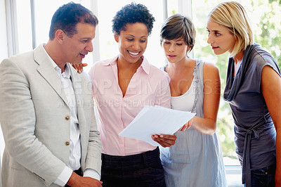 Buy stock photo Young business woman showing document to her successful team
