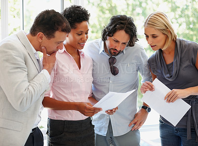 Buy stock photo Group of young business people looking at the report