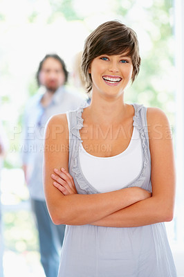 Buy stock photo Woman standing with arms folded with people in background