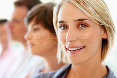 Buy stock photo Focus on happy blonde woman with team in distance