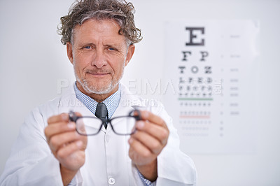 Buy stock photo Portrait of a mature optometrist holding a pair of glasses