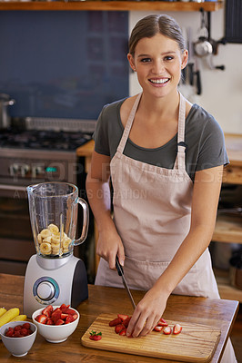 Buy stock photo Portrait of an attractive young woman chopping fruit to make a smoothie